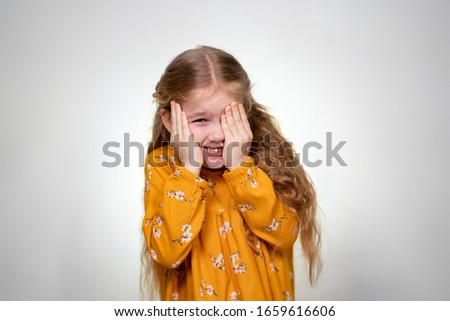 The little girl covers her eyes and mouth with her hand. Baby posing in a yellow dress on a white wall background. #1659616606