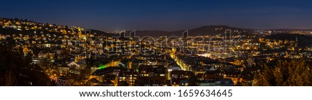 Germany, XXL panorama of magical city stuttgart, houses, churches, and skyline of illuminated buildings from above by night with full moon moonlight #1659634645