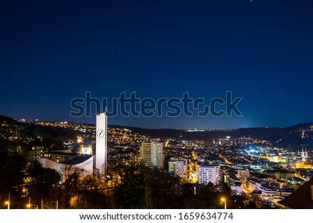 Germany, Beautiful aerial view above stuttgart city houses, church and skyline in basin, illuminated by night in light of fullmoon with starry sky #1659634774