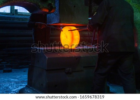 close-up picture of hot steel manual forging process with big mechanical hammer machine