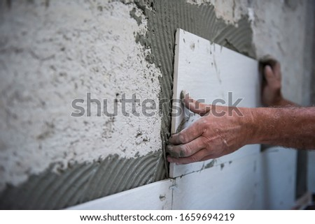 experienced senior construction worker installing big ceramic tiles on interior concrete walls #1659694219