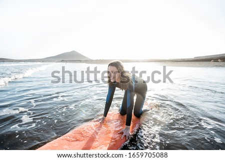 Young surfer in wetsuit getting on surfboard, catching water flow near the beach during a sunset. Water sports and active lifestyle concept #1659705088