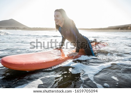 Young surfer in wetsuit getting on surfboard, catching water flow near the beach during a sunset. Water sports and active lifestyle concept #1659705094