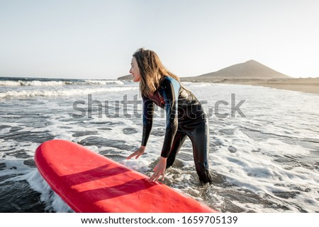 Young surfer in wetsuit getting on surfboard, catching water flow near the beach during a sunset. Water sports and active lifestyle concept #1659705139