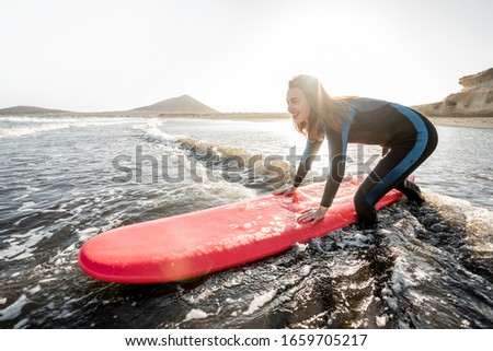 Young surfer in wetsuit getting on surfboard, catching water flow near the beach during a sunset. Water sports and active lifestyle concept #1659705217
