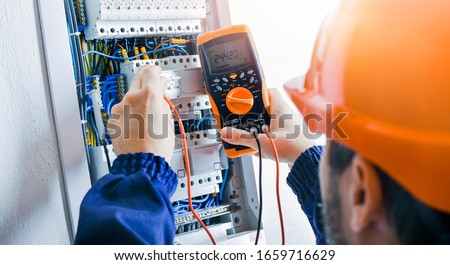 Electrician installing electric cable wires and fuse switch box. Multimeter in hands of electricians detail. #1659716629