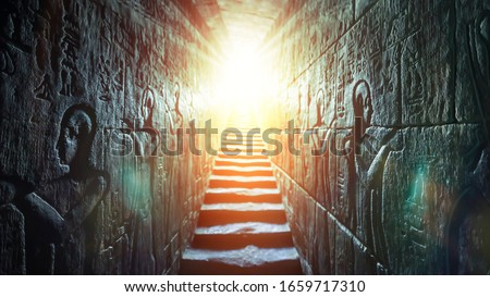 Egypt Edfu temple, Aswan. Passage flanked by two glowing walls full of Egyptian hieroglyphs, illuminated by a warm orange backlight from a door Royalty-Free Stock Photo #1659717310