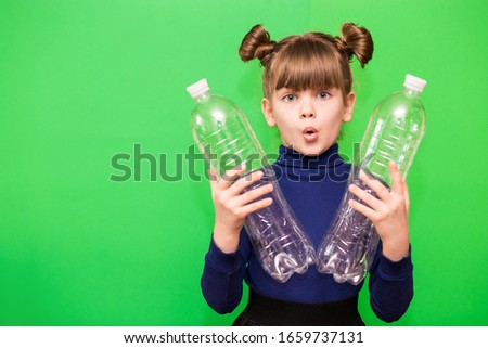 Photo of confused funny little girl holding plastic bottles and looking at camera isolated over green background. ecology concept #1659737131
