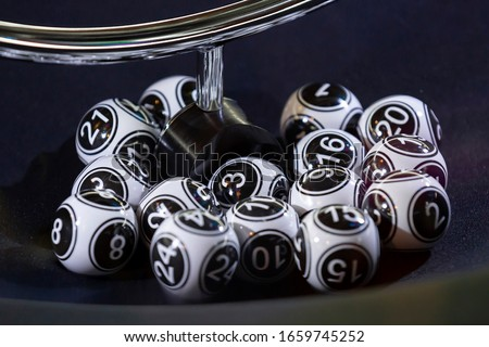 Black and white lottery balls in a bingo machine. Lottery balls in a sphere in motion. Gambling machine and euqipment. #1659745252
