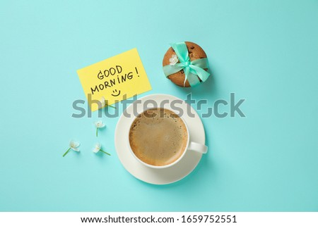 Delicious coffee, cookies, flowers and card with GOOD MORNING wish on light blue background, flat lay
