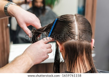 Close up back view hairdresser combing wet hair of woman. #1659761158