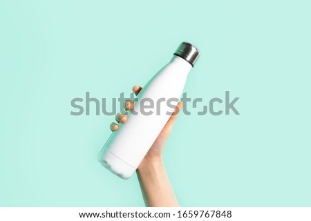 Close-up of female hand, holding white reusable steel stainless eco thermo water bottle with mockup, isolated on background of cyan, aqua menthe color. Be plastic free. Zero waste. #1659767848