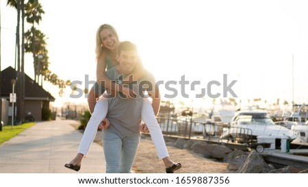 A man gives his beautiful wife a piggy back ride. #1659887356
