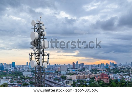 Telecommunication tower with 5G cellular network antenna on city background Royalty-Free Stock Photo #1659895696