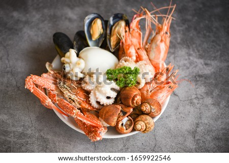 Seafood shrimps prawns squid mussels spotted babylon shellfish crab  on plate and dark background / Cooked food served seafood buffet concept  #1659922546
