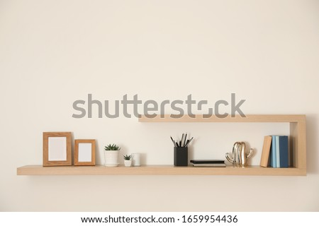 Wooden shelves with books, photo frames and decorative elements on light wall Royalty-Free Stock Photo #1659954436