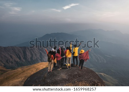 Hiking travellers group colorful shirts standing at the middle of a golden meadow mountain biew. Pointing your finger to their own destination. At Mulayit Taung in Myanmar. #1659968257