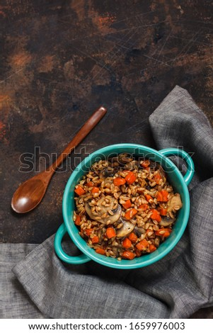 Spelt with mushrooms, carrots and spices in a clay plate on a textured background.This is a very useful product. In the diet, spelt is used for baking, first dishes #1659976003