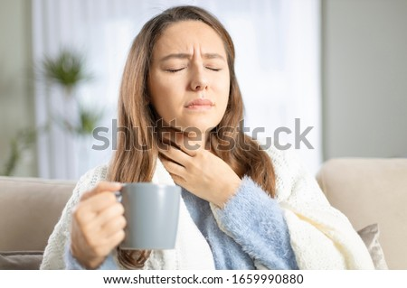 Young woman touching painful neck, sore throat for flu, cold and infection Royalty-Free Stock Photo #1659990880