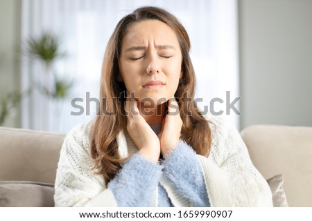 Young woman touching painful neck, sore throat for flu, cold and infection Royalty-Free Stock Photo #1659990907