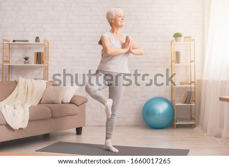 Balance in life. Senior woman doing yoga tree pose at home, free space Royalty-Free Stock Photo #1660017265