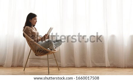 Morning vibes. Girl reading e-book on tablet, sitting in wicker chair against window, panorama with free space #1660017508