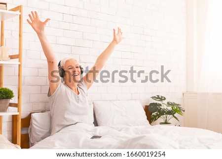 Carefree retirement. Happy senior woman in headphones listening to music, dancing in bed at home, copy space #1660019254