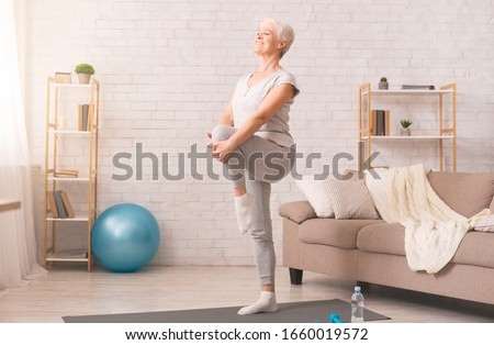 Gym at home. Active senior woman doing legs exercise at home, empty space #1660019572