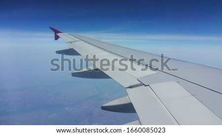 Picture of an airplain wing. The picture is taken out of an aiplain window, and depicts blue sky, and landscapes benethe. The wing is gray, and the tip is red.
