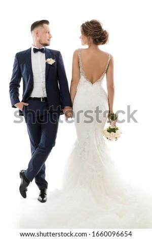 Wedding Couple Studio Portrait, Elegant Groom in Suit Beautiful Bride in White Dress Back Side Royalty-Free Stock Photo #1660096654