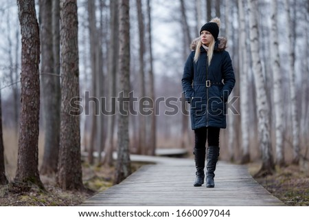 Young woman in dark warm clothes slowly walking on wooden trail at natural park. Cold overcast day. Spending time alone in nature. Peaceful atmosphere. Front view.  Royalty-Free Stock Photo #1660097044