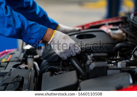 Auto mechanic working in garage.Automotive mechanic male write check items in motor maintenance checklist document. Car repair service concept #1660110508