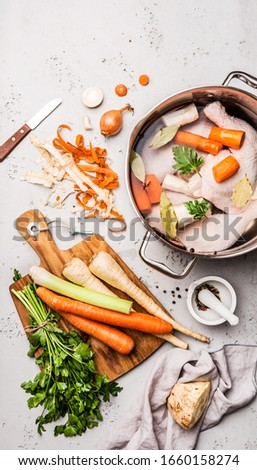 Cooking - preparing chicken stock (broth or bouillon) with vegetables in a pot. Kitchen - grey concrete worktop scenery from above (top view, flat lay).