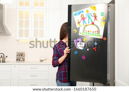 Woman opening refrigerator door with child's drawings, notes and magnets in kitchen. Space for text #1660187650