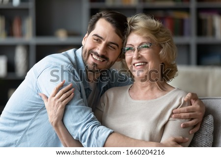 Smiling young man hug middle-aged optimistic mother look in distance dreaming or visualizing together, happy senior 70s mother embrace adult grown-up son enjoy family weekend at home, vision concept #1660204216
