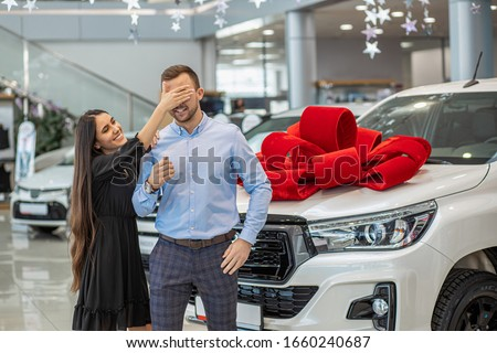 young smiling caucasian couple with new bought dealership. brunette woman closed man's eyes from back, waiting for his reaction to the present #1660240687