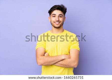 Arabian handsome man over isolated background with arms crossed and looking forward