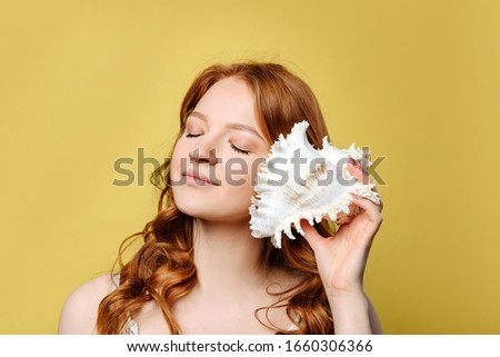 A young woman put a sea shell to her ear. The girl with red hair closed her eyes and listens to the sound of the sea in the sea shell, standing against the wall on a yellow background. #1660306366