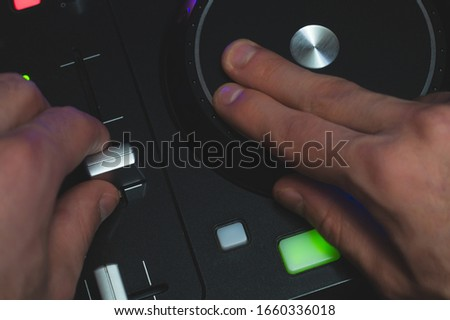 DJ plays music. sound mixer controller with knobs and sliders close up. hands on the mixing deck with turntables at dark with illuminated controls #1660336018