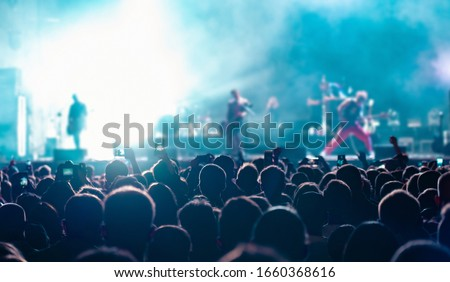 Music fans recording videos on phone in crowd on concert, rear back view of audience people using devices enjoy live music festival event shooting rock band stage on mobile device in blue lights.