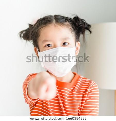 Covid-19 and Air pollution pm2.5 concept.Little chinese girl wearing mask for protect pm2.5 and show pointing finger gesture for stop coronavirus outbreak.Covid-19 and epidemic virus symptoms. #1660384333