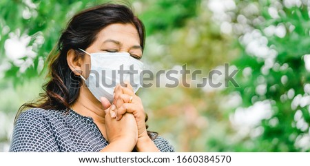 Senior 58 years old indian - iran woman wearing mask for protect pm2.5 and Covid-19.She praying in the morning for a new day freedom to Covid19 virus.Old woman hand praying for thank GOD.Copy space. #1660384570