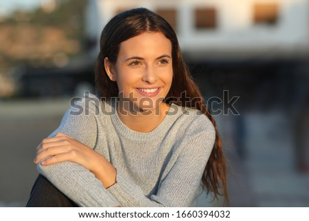 Portrait of a happy teenage girl smiling looking away at sunset in a town #1660394032