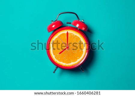Red alarm clock with orange fruit on the place of watch dial.  #1660406281