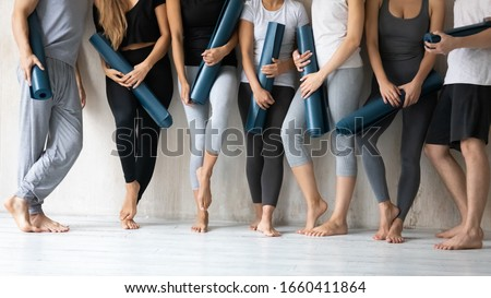 Group of young slim sporty girls and guys wearing comfy stylish sportswear holding personal carpets leaned on wall background waiting for yoga class. Concept of hobby, healthy lifestyle and wellness #1660411864