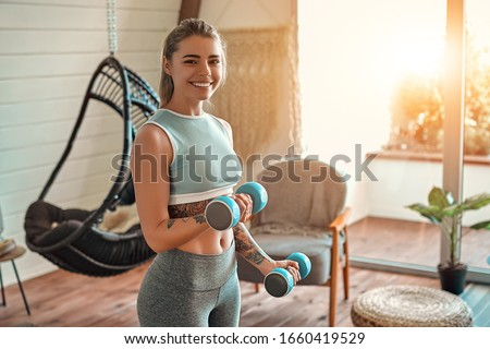 Determined woman losing weight at home and exercising with dumbbells. Sport and recreation concept. Beautiful woman in sportswear with blue dumbbells in her hands. #1660419529
