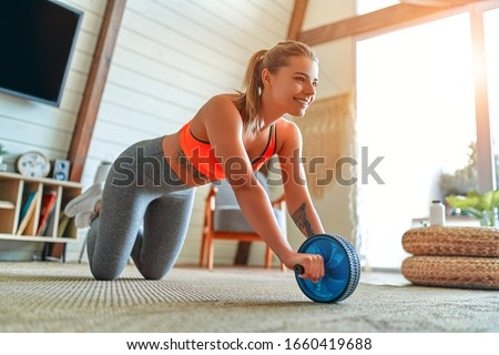 Beautiful strong woman in sportswear is working out with exercise wheel at home in the living room. Sport and recreation concept. #1660419688