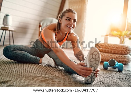 Athletic woman in sportswear doing fitness stretching exercises at home in the living room. Sport and recreation concept. #1660419709