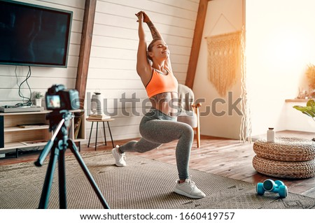Athletic woman blogger in sportswear shoots video on camera as she does exercises at home in the living room. Sport and recreation concept. Healthy lifestyle. #1660419757