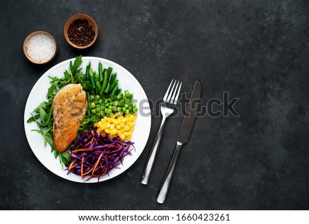 salad of chicken breast, arugula, red cabbage, carrots, corn, green peas, green beans in a white plate on a stone background with copy space for your text #1660423261